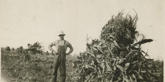 Mack Stateler beside corn shock